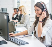 Friendly smiling woman call center operator with headset using computer at office
