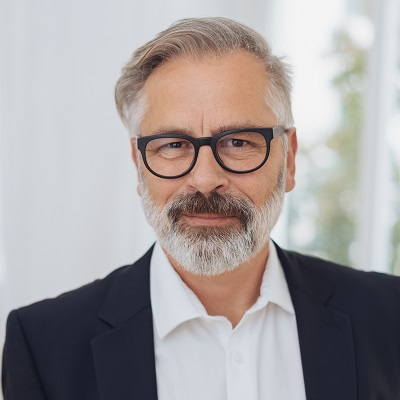 Portrait of elegant mature bearded man with glasses wearing white shirt and jacket